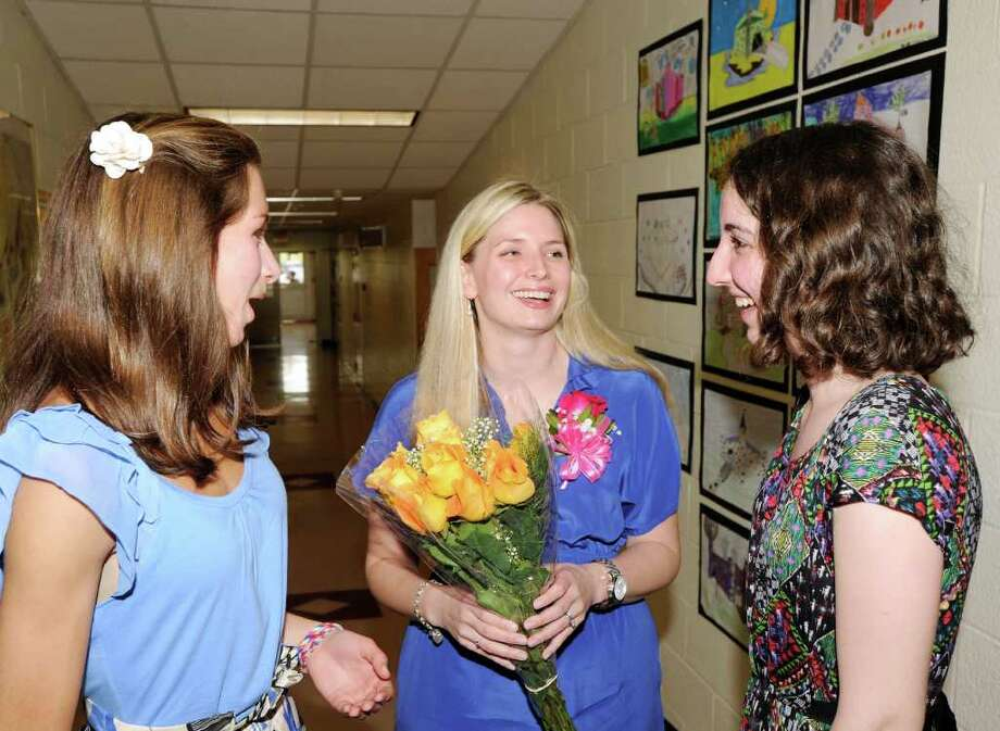 Greenwich High School social studies teacher Karen Boyea, center, holds flowers given to her by Greenwich High School juniors Sarah Fountain, left, 16, and Lily Root, 17, during the Distinguished Teachers Awards Ceremony at Western Middle School in Byram, May 3, 2011. Boyea was one of six teachers honored at the ceremony and has been selected as the district's representative for the 2012 Connecticut Teacher of the Year program. Photo: File Photo / Greenwich Time File Photo