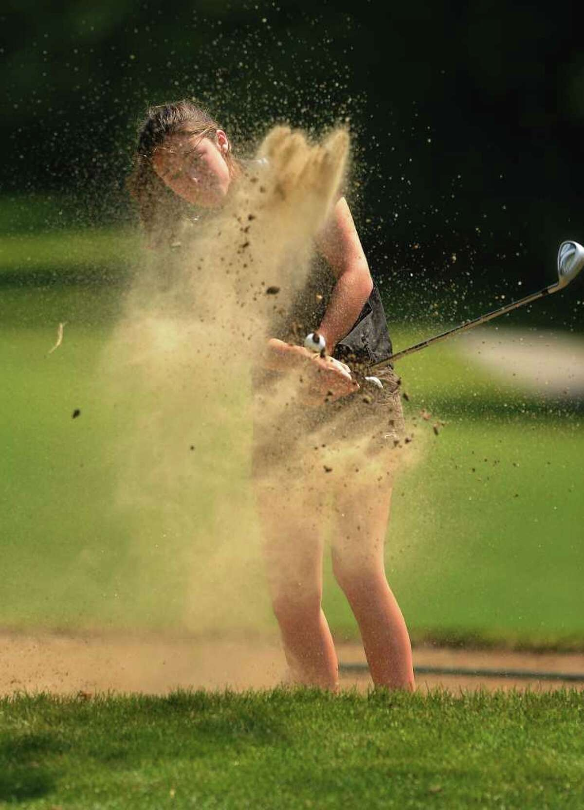 Trumbull's Lauren Gregory blasts out of a greenside bunker on the second hole at the 2011 Girls Golf State Tournament at Orange Hills Country Club in Orange on Tuesday, June 7, 2011.