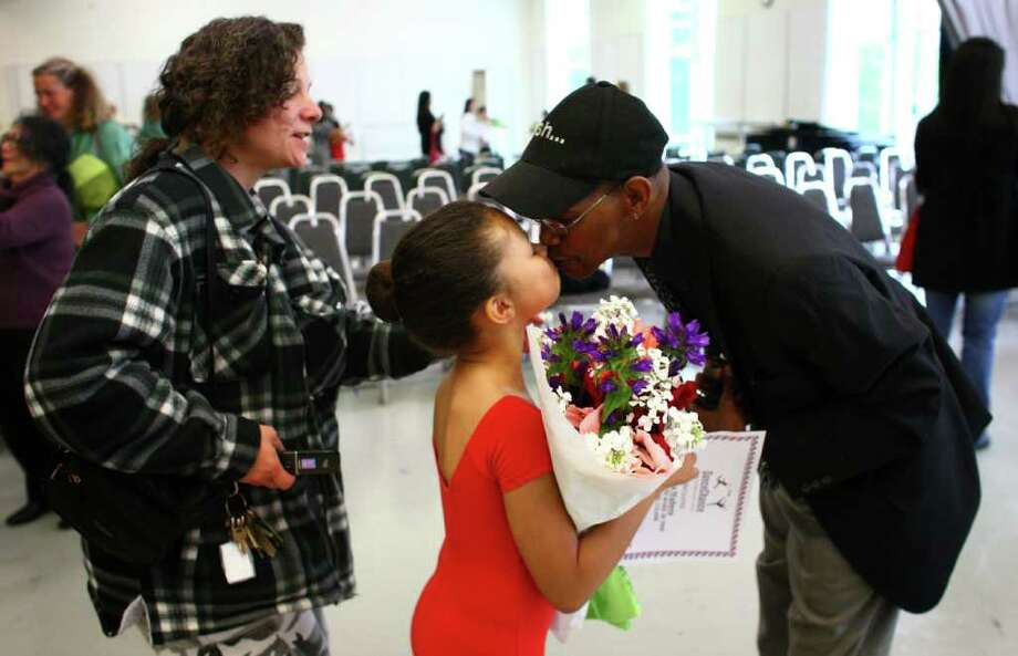 Julianna Walters, 9, gets a kiss from her proud father Jerome Walters after she performed at Pacific Northwest Ballet's 17th annual DanceChance observation day. At left is her mom Rita Walters. Julianna is a student at South Shore K-8. Photo: JOSHUA TRUJILLO / SEATTLEPI.COM