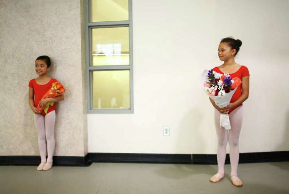 Students Alexis Calonge, left, from Dearborn Park Elementary and Julianna Walters, from South Shore K-8, hold bouquets of flowers after performing at Pacific Northwest Ballet's 17th annual DanceChance observation day on Tuesday. Students in the program showcased what they learned during a show for parents, family, friends and supporters. Students in the program study dance twice per week during the school year. Photo: JOSHUA TRUJILLO / SEATTLEPI.COM