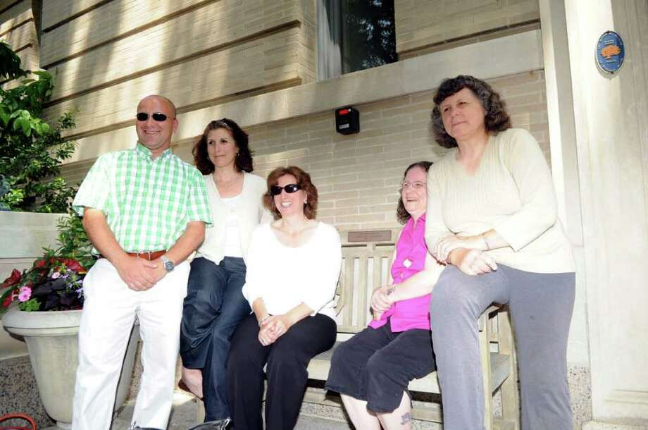 Rose Marzullo's family members sit on a bench dedicated by the Senior Center in Marzullo's memory Tuesday, June 7, 2011.  From left, Marzullo's son, Jim, and daughters Catherine LiVolsi, Diane Olivo, Joanna Sweet, and Christine Krieg.  The center dedicated a second bench in memory of Rose's twin sister, Carmela Pecora. Photo: Helen Neafsey / Greenwich Time