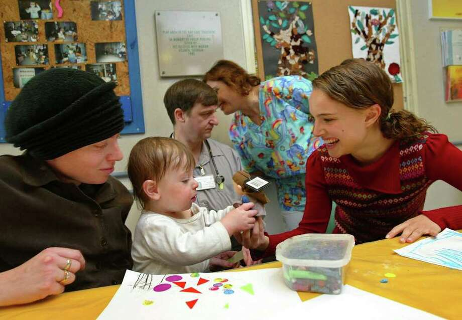 Portman plays with 18-month-old Elkana Hoffbauer next to his mother, Nehama, during a visit to the childrens' ward of Hadassah Hospital on February 17, 2003 in Jerusalem. Portman was born at the hospital. Photo: David Silverman, Getty Images / 2003 Getty Images