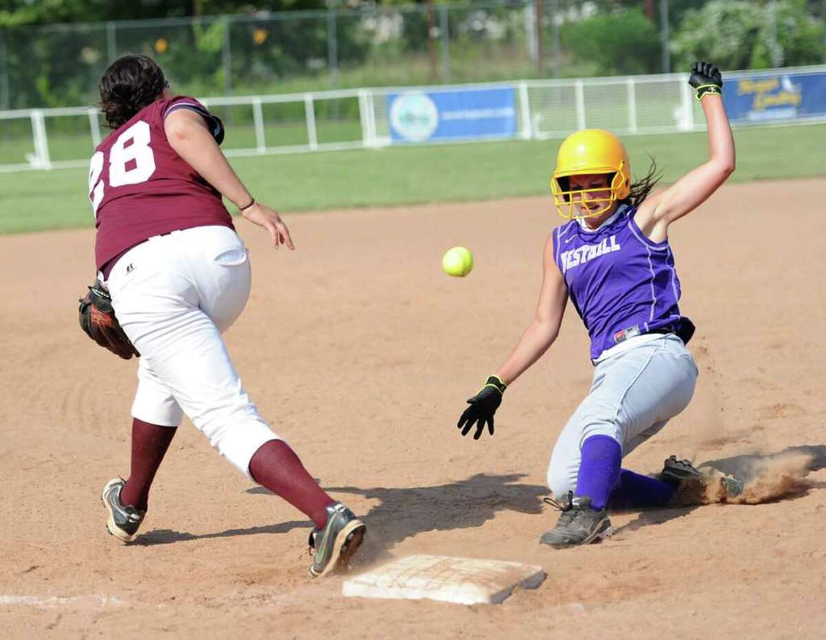 Bristol Central's Jessica Morelli reaches for a ball thrown wide as Westhill's Cassandra Kish slides safely into third before getting up and scoring a run during Tuesday's class LL semifinal game against Bristol Central at DeLuca Field in Stratford on June 7, 2011.