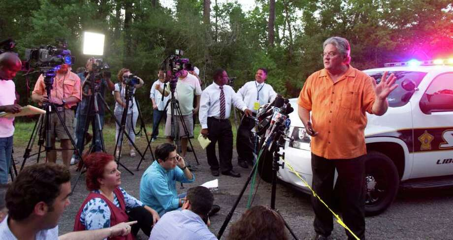 Liberty County Judge Craig McNair alerts the media that the authorities didn't find any dead bodies in a Hardin, Texas farmhouse Tuesday, June 7, 2011, in Daisetta, Texas. Deputies who swarmed the rural Texas neighborhood Tuesday to search the farmhouse where a person claiming to be a psychic told officials multiple bodies were buried found no evidence of even a single homicide, a sheriff's official says. (AP Photo/Houston Chronicle, Nick de la Torre) Photo: Nick De La Torre, MBO / © 2010 Houston Chronicle