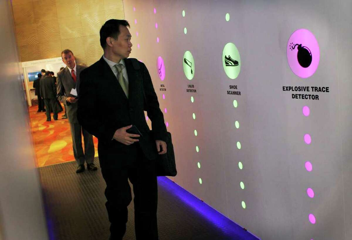 Delegates explore a prototype of an advance security screening system developed by IATA on Tuesday June 7, 2011 in Singapore during a briefing on aviation in a dangerous world at the Air Transport Association (IATA) 67th Annual General Meeting and World Air Transport Summit held in the city-state over three days.(AP Photo/Wong Maye-E)