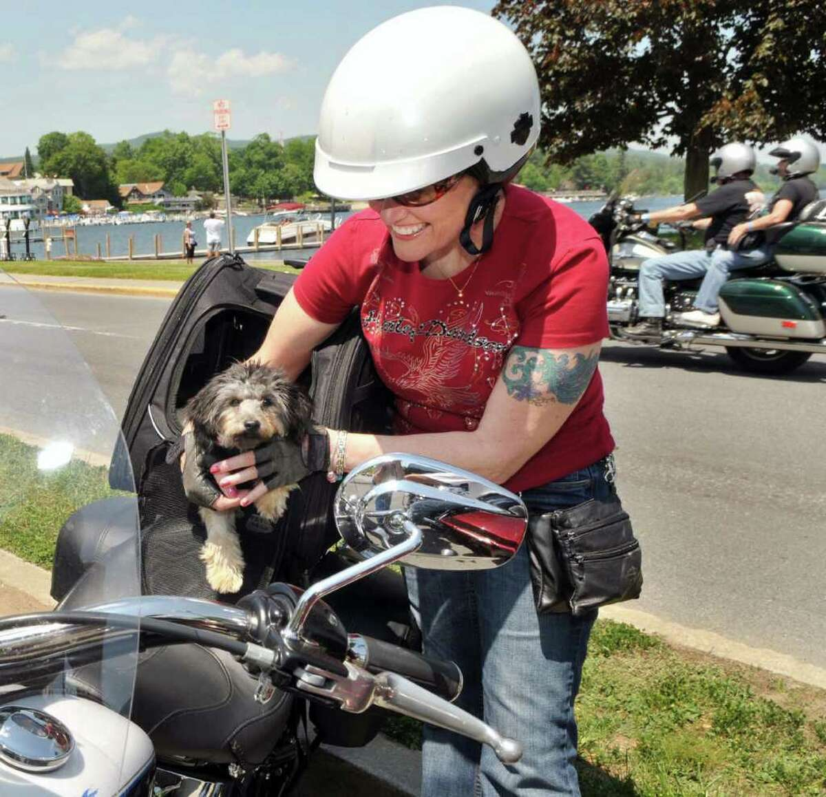 Motorcyclist Michelle Gonsalves of South Paris, Maine fill tucks her 6-month-old puppy