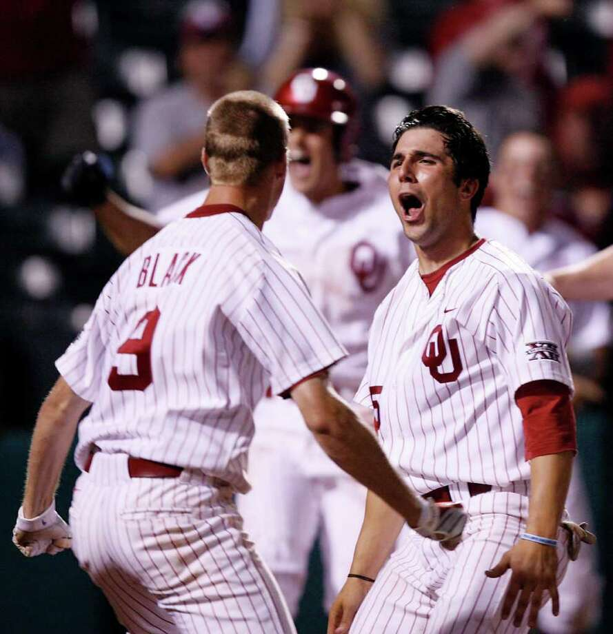 Oklahoma's Tyler Ogle (35) reacts with teammate Danny Black (9) after Ogle's game-winning score during a 2010 game. Ogle, a catcher and 2008 New Braunfels Canyon graduate, was selected in the ninth round by the Los Angeles Dodgers. Photo: AP Photo/The Oklahoman,  Chris Landsberger