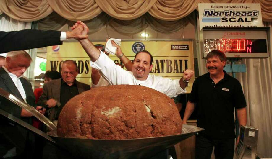 Chef Matthew Mitnitsky cheers after breaking the world record for the largest meatball in Concord, N.H., on Nov. 1, 2009. Mitnitsky, owner of Nonni's Italian Eatery in Concord, said Sunday that a 222.5-pound meatball was authenticated as the world's largest after being weighed by state weights and measures officials. Photo: Jim Cole, AP / AP