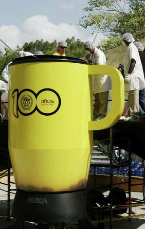 Workers stir 750 gallons of coffee in an oversized coffee mug in Panama City, Sunday, April 1, 2007. A Panamanian coffee company broke the Guinness World Record for the largest cup of coffee.  The last record was set in New York in 2004 with 660.5 gallons. Photo: Arnulfo Franco, AP / AP