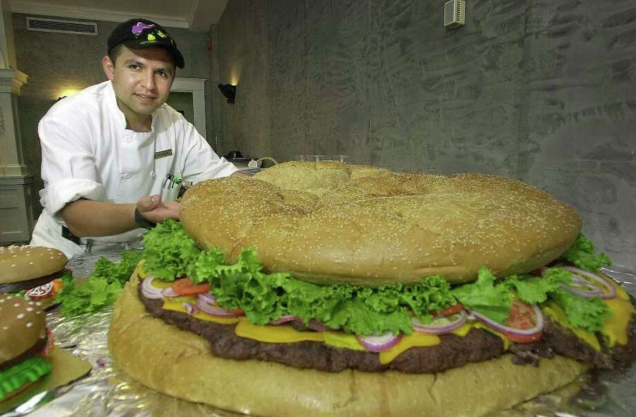 Tremont House Hotel chef Juan Vasquez-Santos shows off what he hopes is the world's largest hamburger at the hotel in Galveston, Texas, on May 25, 2001. The hamburger was prepared to celebrate National Hamburger Month and Vazquez-Santos says it weighs about 185 pounds. It includes 100 pounds of ground beef, a 35-pound bun and at least 50 pounds of cheese, tomatoes, pickles and onions, according to the chef. Photo: KEVIN BARTRAM, AP / THE GALVESTON COUNTY DAILY NEWS