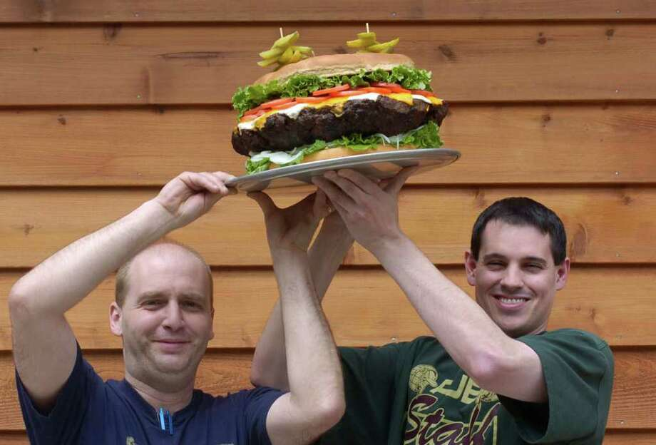 Kitchen manager Matthew Williams (left) and Dennis Liegey III, vice president of Denny's Beer Barrel Pub in Clearfield, Pa., hoist a 15-pound hamburger over their heads in front of the restaurant on May 3, 2005. Dubbed the Beer Barrel Belly Buster, the burger comes with 10.5 pounds of ground beef, 25 slices of cheese, a head of lettuce, three tomatoes, two onions, a cup-and-a-half each of mayonnaise, relish, ketchup, mustard and banana peppers and a bun. It costs $30. Photo: Andy Starnes, AP / POST-GAZETTE