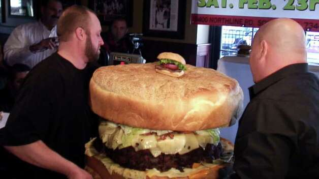Michael Berry, left, and Steve Mallie put a burger on a scale as Mallie's Sports Bar & Grill hoping to set a new world's record for the heaviest hamburger on Saturday, Feb. 23, 2008  in Southgate, Mich. After 12 hours of preparation and baking, the 134-pound (over 60 kilos) burger emerged at Mallie's Sports Bar and Grill on Saturday. Mallie's unofficial record outweighs the 123-pound (over 55 kilos) burger made last year by Denny's Beer Barrel Pub, of Clearfield, Pa. Photo: Ankur Dholakia, AP / The Detroit News