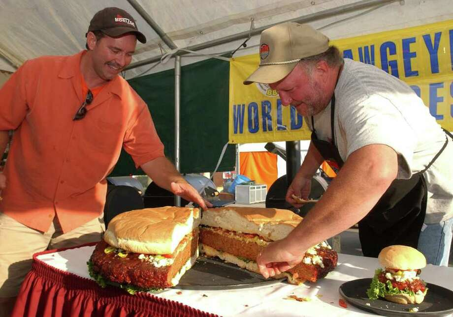 Mike Tucker (right) of Ankeny, Iowa, and Roger Davidson of Perry, Okla., work on an oversized pork burger, on June 9, 2006, in Des Moines, Iowa. Davidson and Tucker concocted the giant burger at the World Pork Expo starting with 35 pounds of sausage and three pounds of blue cheese. Photo: STEVE POPE, AP / AP