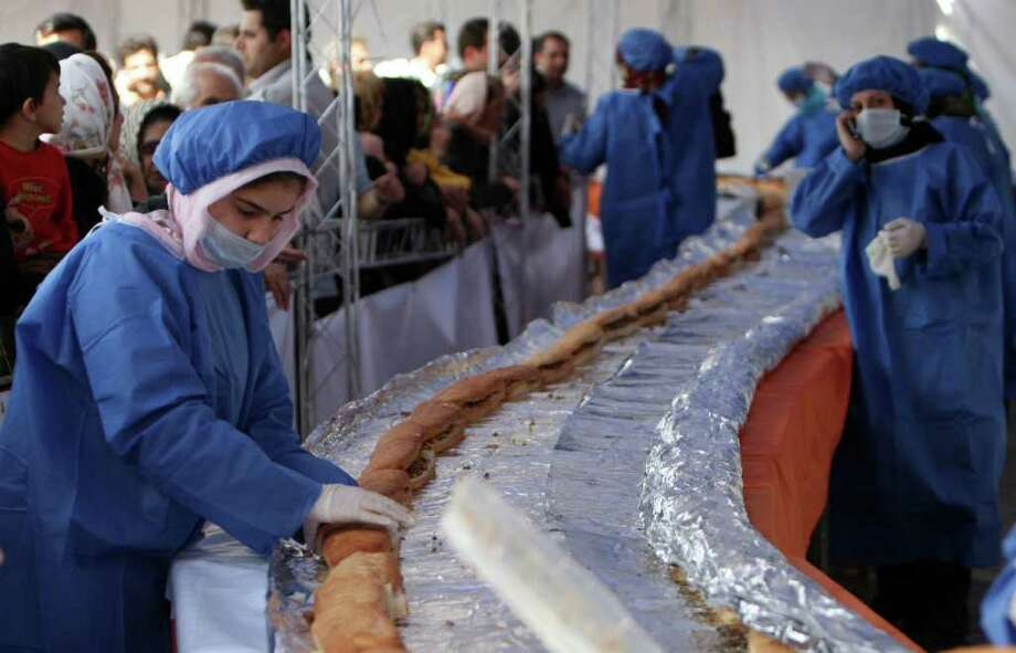 Iranian workers prepare a giant ostrich meat sandwich in an attempt to achieve a Guinness World Record, during the second international food and health festival in Tehran, Iran, on Oct. 17, 2008. About 1,500 cooks will use 2,200 pounds of ostrich meat to make the 4,920 foot-long sandwich to promote Iran's fledgling ostrich farming business and promote healthy eating. Photo: Hasan Sarbakhshian, AP / AP