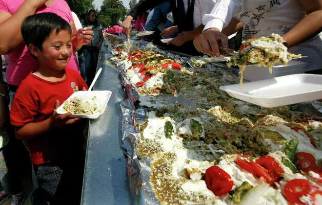 A boy waits to be served a portion of the world's largest 'Enchilada', a traditional Mexican food, during the National Enchilada Fair at the neighborhood of Iztapalapa in Mexico City, Sunday, Oct. 17, 2010. The enchilada, measuring 70 meters long and 1,416 kgs, entered the famous Guinness Record book Sunday. Photo: Marco Ugarte, AP / AP