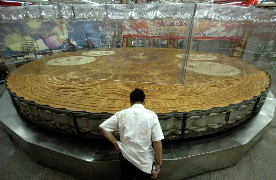 A chef gives a final check on the the largest moon cake in Shenyang, China, on Aug. 21, 2007. The moon cake, which measures nearly 27 feet in diameter, eight inches thick and weighs nearly 13 tons, has 10 flavors. It was made with one ton of flour and 12 tons of stuffing, and baked for 10 hours. Photo: AP / CHINATOPIX