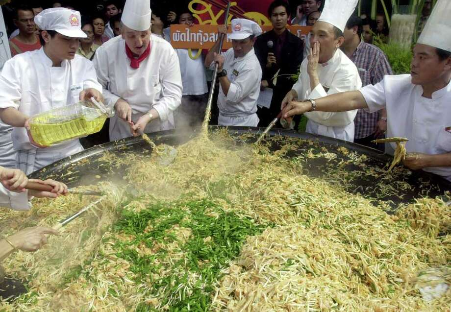 Thai and foreign chefs join hands in cooking the world's biggest Pad Thai (or fried noodle Thai style) outside a shopping mall in Bangkok, Thailand on June 3, 2004. Fifteen chefs from local and international restaurants in Bangkok and abroad gathered around a diameter of 7.75 feet pan, cooking the dish with a mixing of 68 pounds of white noodles, 840 eggs, 63 pounds of shrimp plus some of the vegetables which can serve 1,200 people. Photo: APICHART WEERAWONG, AP / AP
