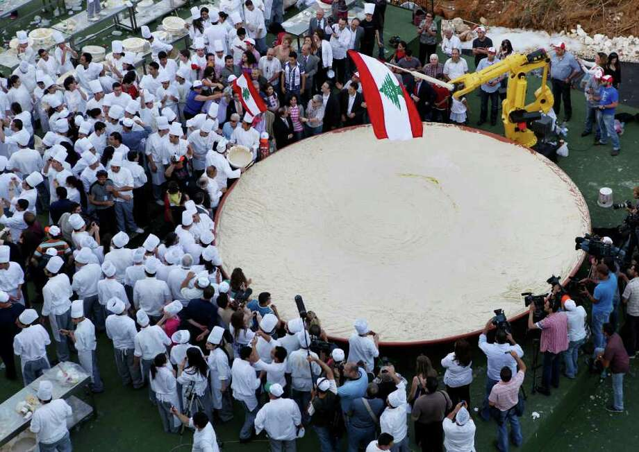 Lebanese chefs celebrate after preparing a massive bowl of hummus weighing 22,046 pounds, the size of Lebanon in square kilometers, during a bid to break a record previously held by Israel and reclaim ownership over the popular Middle Eastern dish, in Fanar, east of Beirut, Lebanon, on May 8, 2010. Some 300 Lebanese chefs prepared the huge hummus plate and a Guinness World Records adjudicator confirmed that Lebanon now holds the record. Photo: HUSSEIN MALLA, AP / AP