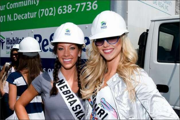 Micaela Johnson, Miss Nebraska USA 2008, and Candice Crawford, Miss Missouri USA 2008, pose for a photo in their hard hats at 