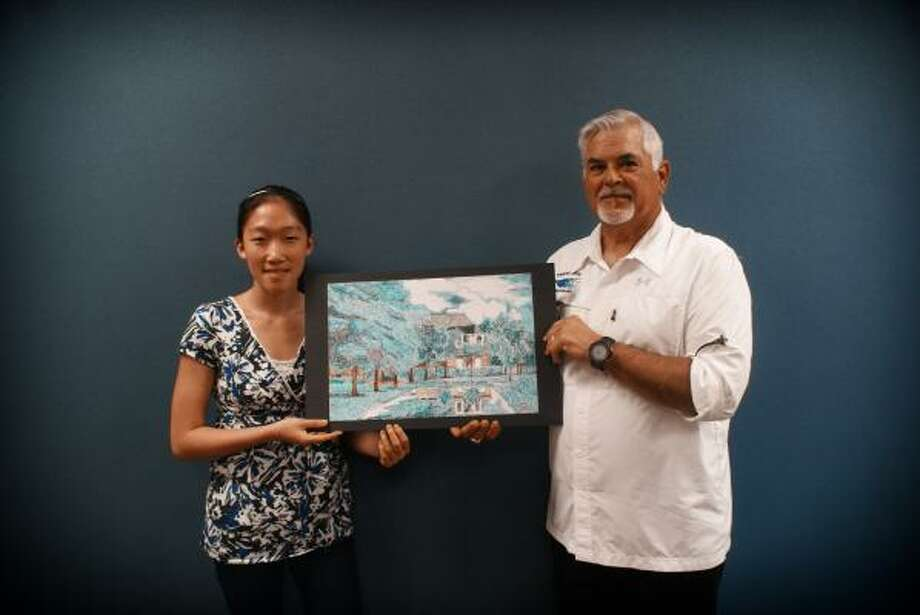 CHOSEN ARTWORK: Friendswood Junior High Principal Dana Drew stands with Molly Chen, who is holding the artwork that he bought to hang at the school. Photo: Friendswood ISD