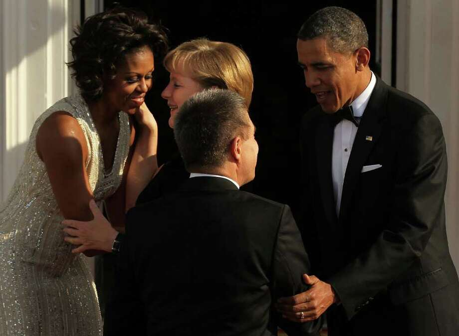 U.S. President Barack Obama (R) and first lady Michelle Obama (L) greet German Chancellor Angela Merkel (2nd L) and her husband Joachim Sauer (3rd L) on the North Portico before a state dinner at the White House June 7, 2011 in Washington, DC. This is the first official visit by a European leader to the White House since Obama became president. Merkel will be presented with the 2010 Medal of Freedom at a state dinner tonight. Photo: Alex Wong, Getty Images / 2011 Getty Images