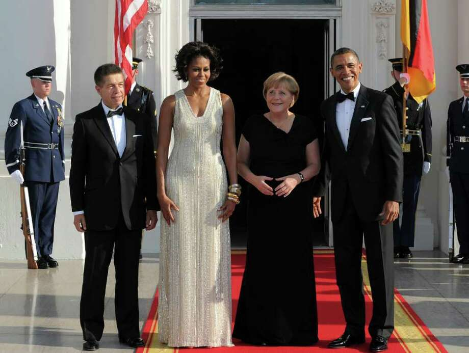 US President Barack Obama (R) and First Lady Michelle Obama (2nd-L) greet German Chancellor Angela Merkel (2nd-R) and her husband Joachim Sauer (L) at the North Portico of the White House in Washington, DC, on June 7, 2011 for the State Dinner. Obama warned Europe's debt crisis must not destabilize the global economy, as he laid on a lavish and warm White House welcome for Merkel. Obama said he and Merkel had extensive talks about the plight of debt-stricken Greece, which needs a second huge financial bailout, despite some reluctance from some eurozone members to stump up fresh funds. AFP Photo/Jewel Samad Photo: JEWEL SAMAD, AFP/Getty Images / 2011 AFP