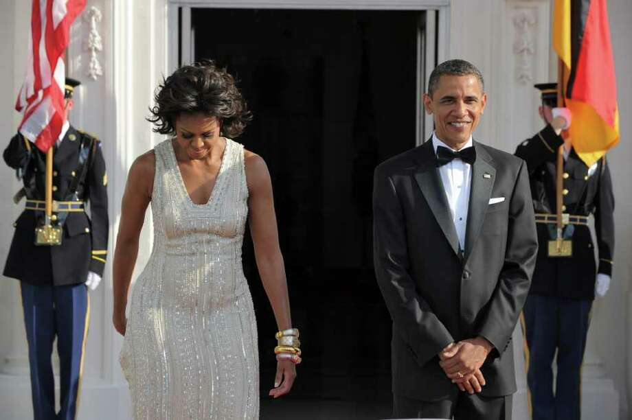 US President Barack Obama (R) and First Lady Michelle Obama arrive to greet German Chancellor Angela Merkel and her husband Joachim Sauer (not in picture) at the North Portico of the White House in Washington, DC, on June 7, 2011 for the State Dinner. Obama warned Europe's debt crisis must not destabilize the global economy, as he laid on a lavish and warm White House welcome for Merkel. Obama said he and Merkel had extensive talks about the plight of debt-stricken Greece, which needs a second huge financial bailout, despite some reluctance from some eurozone members to stump up fresh funds. AFP Photo/Jewel Samad Photo: JEWEL SAMAD, AFP/Getty Images / 2011 AFP