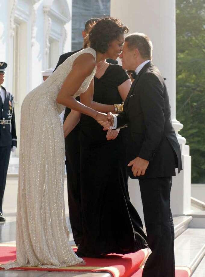 US President Barack Obama and First Lady Michelle Obama greet German Chancellor Angela Merkel and her husband Joachim Sauer at the North Portico of the White House in Washington, DC, on June 7, 2011 for the State Dinner. Obama warned Europe's debt crisis must not destabilize the global economy, as he laid on a lavish and warm White House welcome for Merkel. Obama said he and Merkel had extensive talks about the plight of debt-stricken Greece, which needs a second huge financial bailout, despite some reluctance from some eurozone members to stump up fresh funds. AFP Photo/Saul Loeb Photo: SAUL LOEB, AFP/Getty Images / 2011 AFP