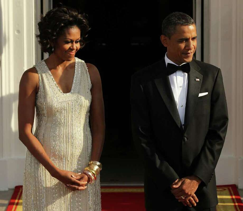 U.S. President Barack Obama (R) and first lady Michelle Obama (L) wait for the arrival of German Chancellor Angela Merkel and her husband Joachim Sauer on the North Portico before a state dinner at the White House June 7, 2011 in Washington, DC. This is the first official visit by a European leader to the White House since Obama became president. Merkel will be presented with the 2010 Medal of Freedom at a state dinner tonight. Photo: Alex Wong, Getty Images / 2011 Getty Images
