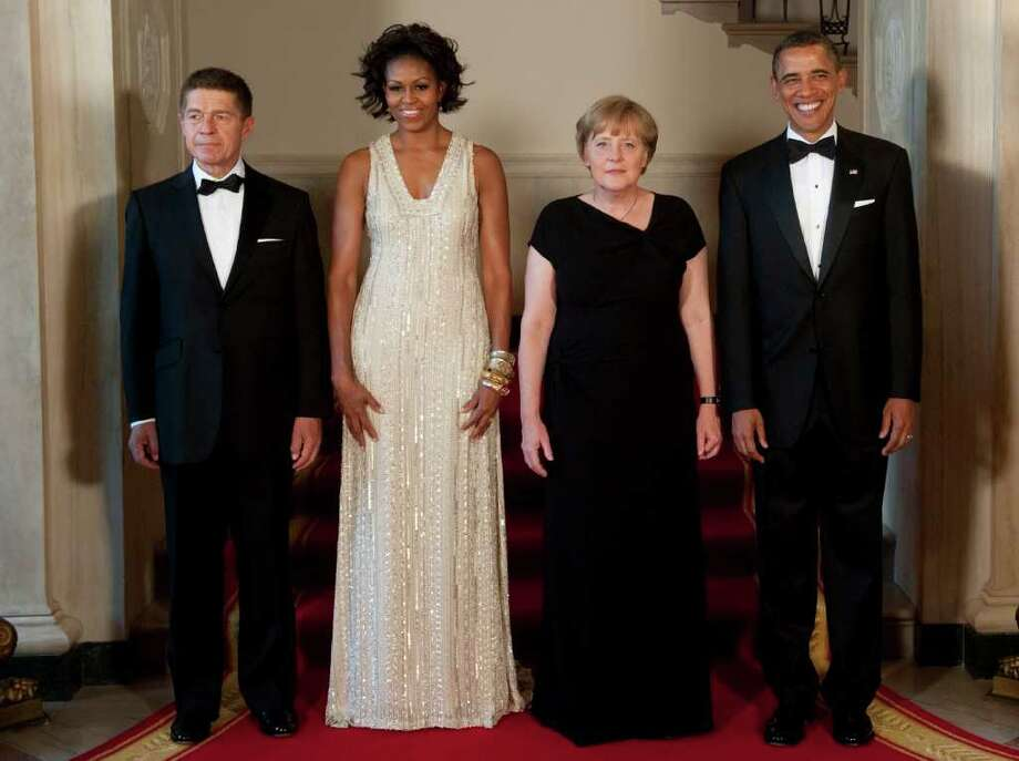 US President Barack Obama (R) and First Lady Michelle Obama (2nd-L) stand alongside German Chancellor Angela Merkel (2nd-R) and her husband, Joachim Sauer, in the Grand Foyer of the White House in Washington, DC, June 7, 2011, prior to a State Dinner. AFP PHOTO / Saul LOEB Photo: SAUL LOEB, AFP/Getty Images / 2011 AFP