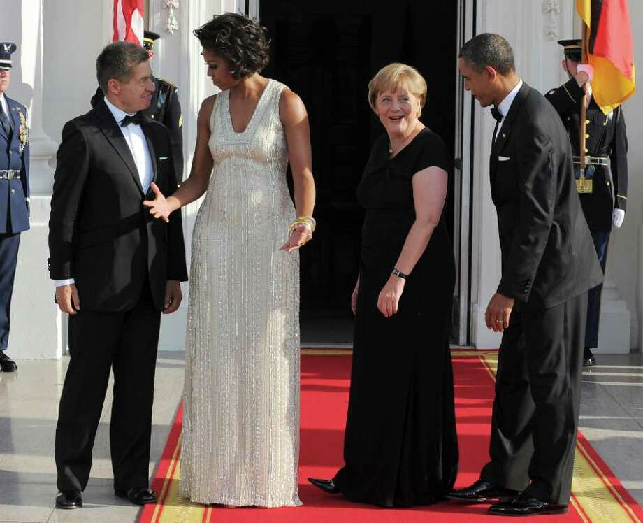 US President Barack Obama and First Lady Michelle Obama greet German Chancellor Angela Merkel and her husband Joachim Sauer at the North Portico of the White House in Washington, DC, on June 7, 2011 for the State Dinner. Obama warned Europe's debt crisis must not destabilize the global economy, as he laid on a lavish and warm White House welcome for Merkel. Obama said he and Merkel had extensive talks about the plight of debt-stricken Greece, which needs a second huge financial bailout, despite some reluctance from some eurozone members to stump up fresh funds. AFP Photo/Jewel Samad Photo: JEWEL SAMAD, AFP/Getty Images / 2011 AFP