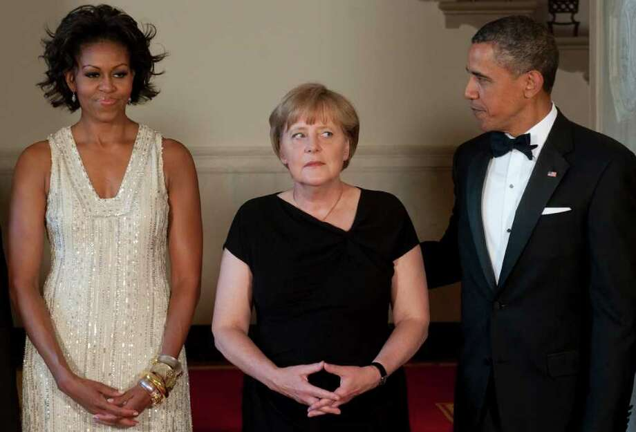 US President Barack Obama (L) and First Lady Michelle Obama (R) stand alongside German Chancellor Angela Merkel and in the Grand Foyer of the White House in Washington, DC, June 7, 2011, prior to a State Dinner as part of an official visit. AFP PHOTO / Saul LOEB Photo: SAUL LOEB, AFP/Getty Images / 2011 AFP