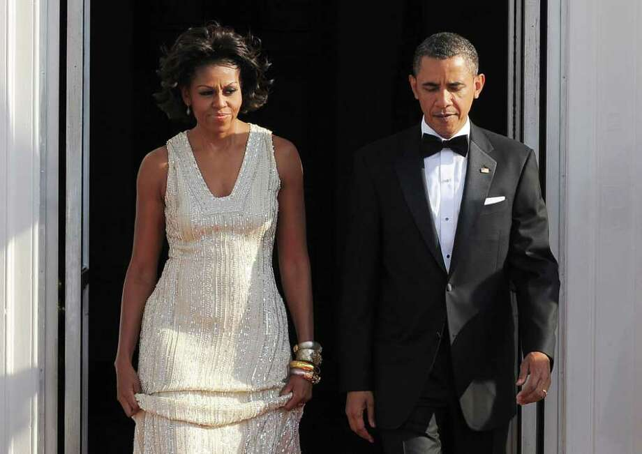 US President Barack Obama and First Lady Michelle Obama arrive to greet German Chancellor Angela Merkel and her husband Joachim Sauer at the North Portico of the White House in Washington, DC, on June 7, 2011 for the State Dinner. Obama warned Europe's debt crisis must not destabilize the global economy, as he laid on a lavish and warm White House welcome for Merkel. Obama said he and Merkel had extensive talks about the plight of debt-stricken Greece, which needs a second huge financial bailout, despite some reluctance from some eurozone members to stump up fresh funds. AFP Photo/Jewel Samad Photo: JEWEL SAMAD, AFP/Getty Images / 2011 AFP