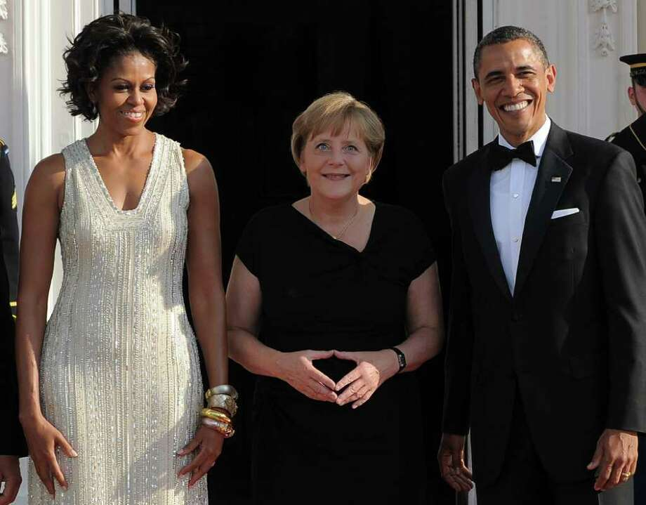 US President Barack Obama (R) and First Lady Michelle Obama greet German Chancellor Angela Merkel at the North Portico of the White House in Washington, DC, on June 7, 2011 for the State Dinner. Obama warned Europe's debt crisis must not destabilize the global economy, as he laid on a lavish and warm White House welcome for Merkel. Obama said he and Merkel had extensive talks about the plight of debt-stricken Greece, which needs a second huge financial bailout, despite some reluctance from some eurozone members to stump up fresh funds. AFP Photo/Jewel Samad Photo: JEWEL SAMAD, AFP/Getty Images / 2011 AFP