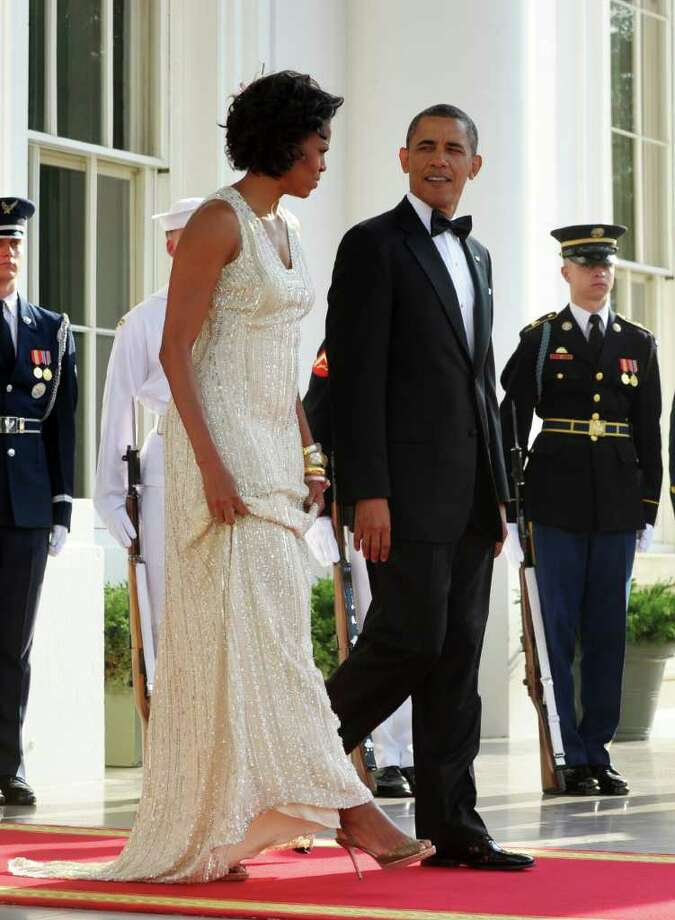 US President Barack Obama and First Lady Michelle Obama arrive to greet German Chancellor Angela Merkel and her husband Joachim Sauer (out of frame) at the North Portico of the White House in Washington, DC, June 7, 2011 for the State Dinner. Obama warned Europe's debt crisis must not destabilize the global economy, as he laid on a lavish and warm White House welcome for Merkel. Obama said he and Merkel had extensive talks about the plight of debt-stricken Greece, which needs a second huge financial bailout, despite some reluctance from some eurozone members to stump up fresh funds. AFP Photo/Saul Loeb Photo: SAUL LOEB, AFP/Getty Images / 2011 AFP