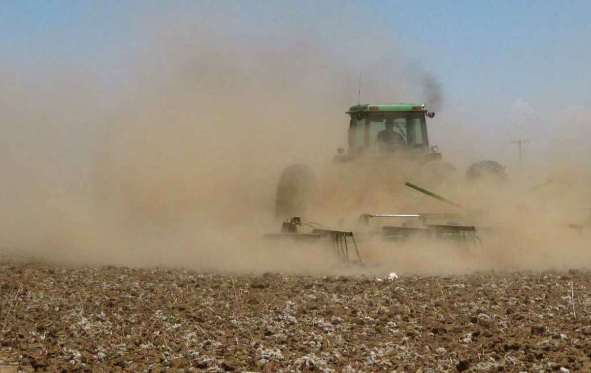 In this May 19, 2011 photo, Tyler Gray stirs up a cloud of dust as pulls a tiller across a dry cotton field near Lubbock, Texas, trying to break up hardened ground. A historic drought has already cost Texas farmers and ranchers an estimated $1.5 billion, and the cost is growing daily as parched conditions persist in much of the state.