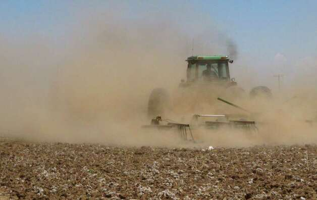 In this May 19, 2011 photo, Tyler Gray stirs up a cloud of dust as pulls a tiller across a dry cotton field near Lubbock, Texas, trying to break up hardened ground. A historic drought has already cost Texas farmers and ranchers an estimated $1.5 billion, and the cost is growing daily as parched conditions persist in much of the state. Photo: Betsy Blaney, AP / AP