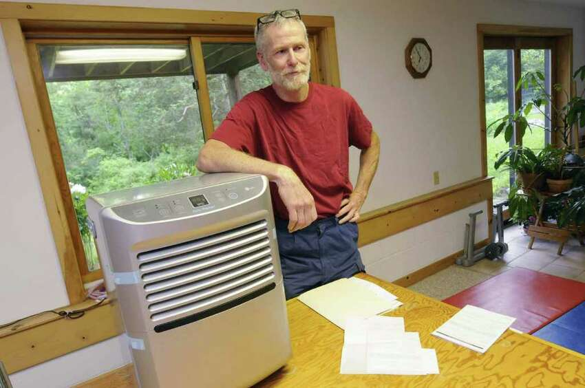 Joe Okoniewski with the dehumidifier that was twice replaced, under warranty. But each time, instead of a new unit, they were sent a used and refurbished unit in Altamont, NY Tuesday June 7, 2011.( Michael P. Farrell/Times Union )