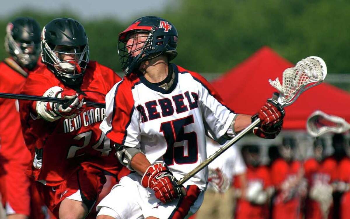 New Fairfield's #15 Dylan White, right, works to get past New Canaan's #24 Michael Root, during CIAC Class M semifinal boys lacrosse action at Fairfield Warde High in Fairfield, Conn. on Wednesday June 8, 2011.