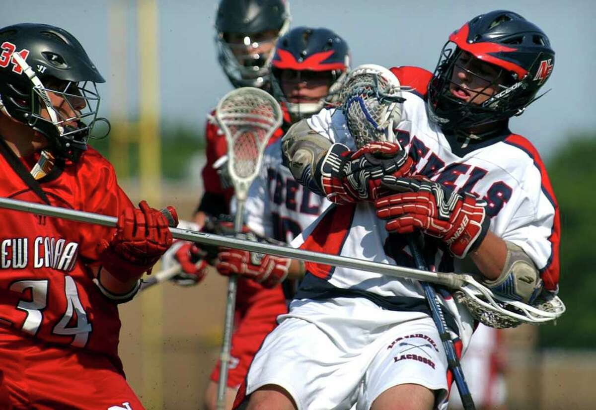 New Canaan's #34 Kevin McDonough, left, attempts to knock away the ball from New Fairfield's #26 Grag Castro, during CIAC Class M semifinal boys lacrosse action at Fairfield Warde High in Fairfield, Conn. on Wednesday June 8, 2011.