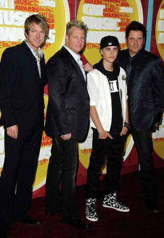 NASHVILLE, TN - JUNE 08:  (L-R) Musicians Jay DeMarcus, Gary LeVox, Justin Bieber and Joe Don Rooney attend the 2011 CMT Music Awards at the Bridgestone Arena on June 8, 2011 in Nashville, Tennessee. Photo: Jason Merritt, Getty Images / 2011 Getty Images