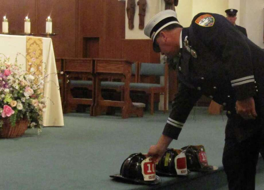 A firefighter places a helmet on the altar of Assumption Church in Westport during a memorial service for fallen firefighters Tuesday. Photo: Kirk Lang / Westport News