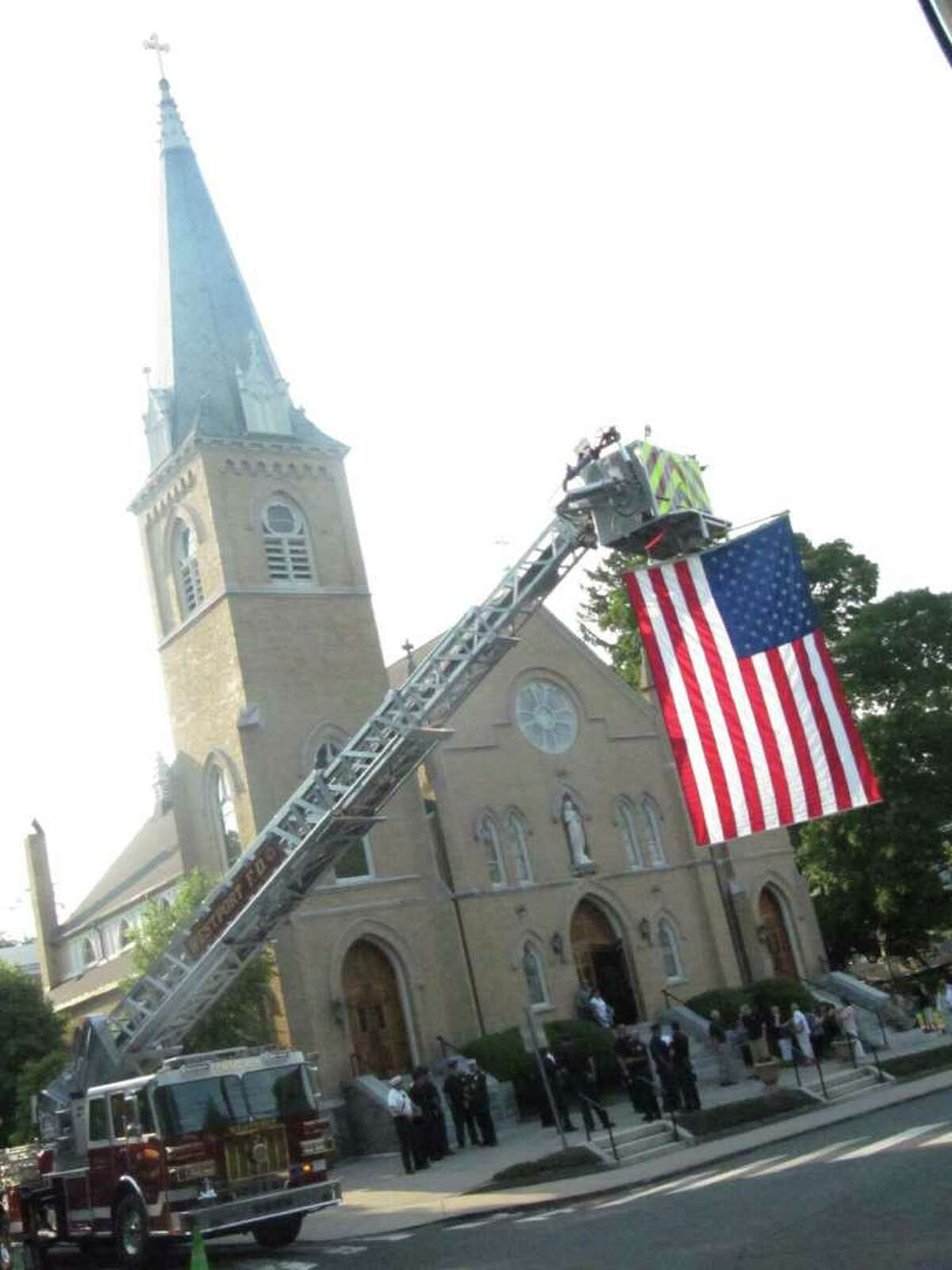 An American flag is unfurled from a Westport Fire Department ladder truck in front of Assumption Church where a memorial service took place Tuesday night for firefighters who died in the line of duty.