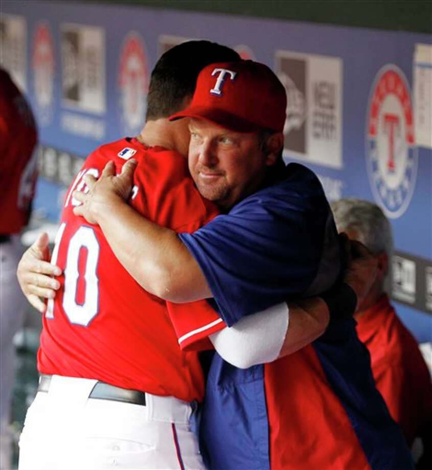 Texas Rangers Michael Young (10) hugs new batting coach Scott Coolbaugh in the dugout during the third inning of a baseball game against the Detroit Tigers at Rangers Ballpark in Arlington, Texas, Wednesday June 8, 2011. Coolbaugh replaced Thad Bosley as hitting coach after Bosley was fired on Wednesday. (AP Photo/Sharon Ellman) Photo: Sharon Ellman, Associated Press / FR170032 AP