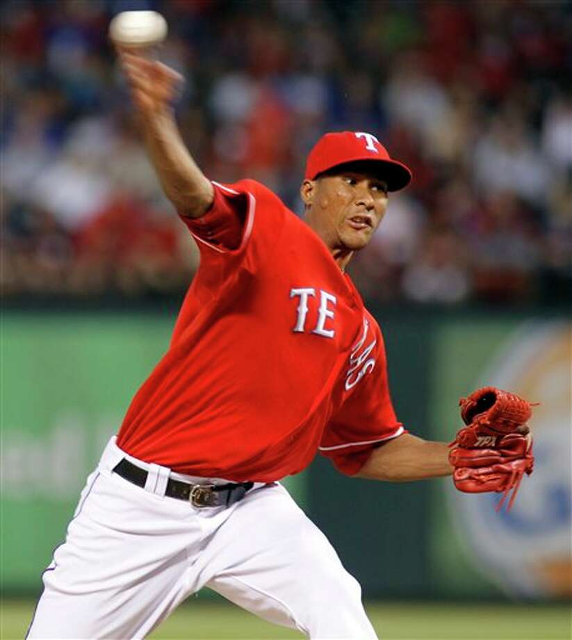 Texas Rangers pitcher Alexi Ogando throws a pitch in the fifth inning during a major league baseball game against the Detroit Tigers at Rangers Ballpark in Arlington, Texas, Wednesday June 8, 2011. (AP Photo/Sharon Ellman) Photo: Sharon Ellman, Associated Press / FR170032 AP