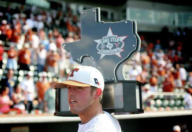 Texas closing pitcher Austin Wood hoists the Lonestar Classic trophy after pitching against Texas A&M during the final game of the  series in Austin on May 10, 2009. Texas won 5-4. Benjamin Sklar/San Antonio Express-News Photo: Benjamin Sklar, Longhorns / Benjamin Sklar