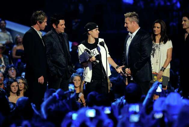 NASHVILLE, TN - JUNE 08:  Musician Joe Don Rooney (L), Jay DeMarcus, Gary LeVox (R) of Rascal Flatts and musician Justin Bieber (C) accept Collaborative Video of the Year award on stage at the 2011 CMT Music Awards at the Bridgestone Arena on June 8, 2011 in Nashville, Tennessee. Photo: Jason Merritt, Getty Images / 2011 Getty Images