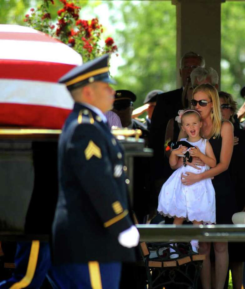 Jessica Bohall and daughter Annabelle, 4, watch Wednesday as a caisson carrying the casket of her husband, Army Sgt. Thomas Bohall, rolls by at Fort Sam Houston National Cemetery. Sgt. Bohall, a Kentucky soldier and 2004 Reagan graduate who considered San Antonio his home, died May 26 in an insurgent attack in Afghanistan. Photo: Billy Calzada/Express-News / gcalzada@express-news.net