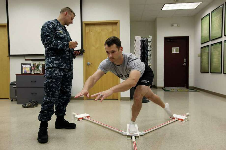 """Lt. Mark Riebel (left) monitors Lt. George Clevenger at Fort Sam as he maneuvers with a """"Y"""" balance kit that can identify asymmetries, or limited range of motion. Photo: Jerry Lara/Express-News / SAN ANTONIO EXPRESS-NEWS"""