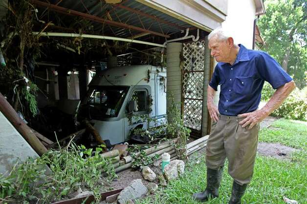 METRO  Fred Maxwell takes a grim look at his ruined RV which was trapped in the Guadalupe River flooding.  Maxwell's home on Fair Ln. was built in 2002 - 2003 after the last big flood. It withstood the force of the latest flood, but the interior was soaked with about one foot of floodwater on the ground level.  Flood clean up in New Braunfels on June 10, 2010.  Tom Reel/Staff Photo: TOM REEL, SAN ANTONIO EXPRESS-NEWS / © 2010 San Antonio Express-News